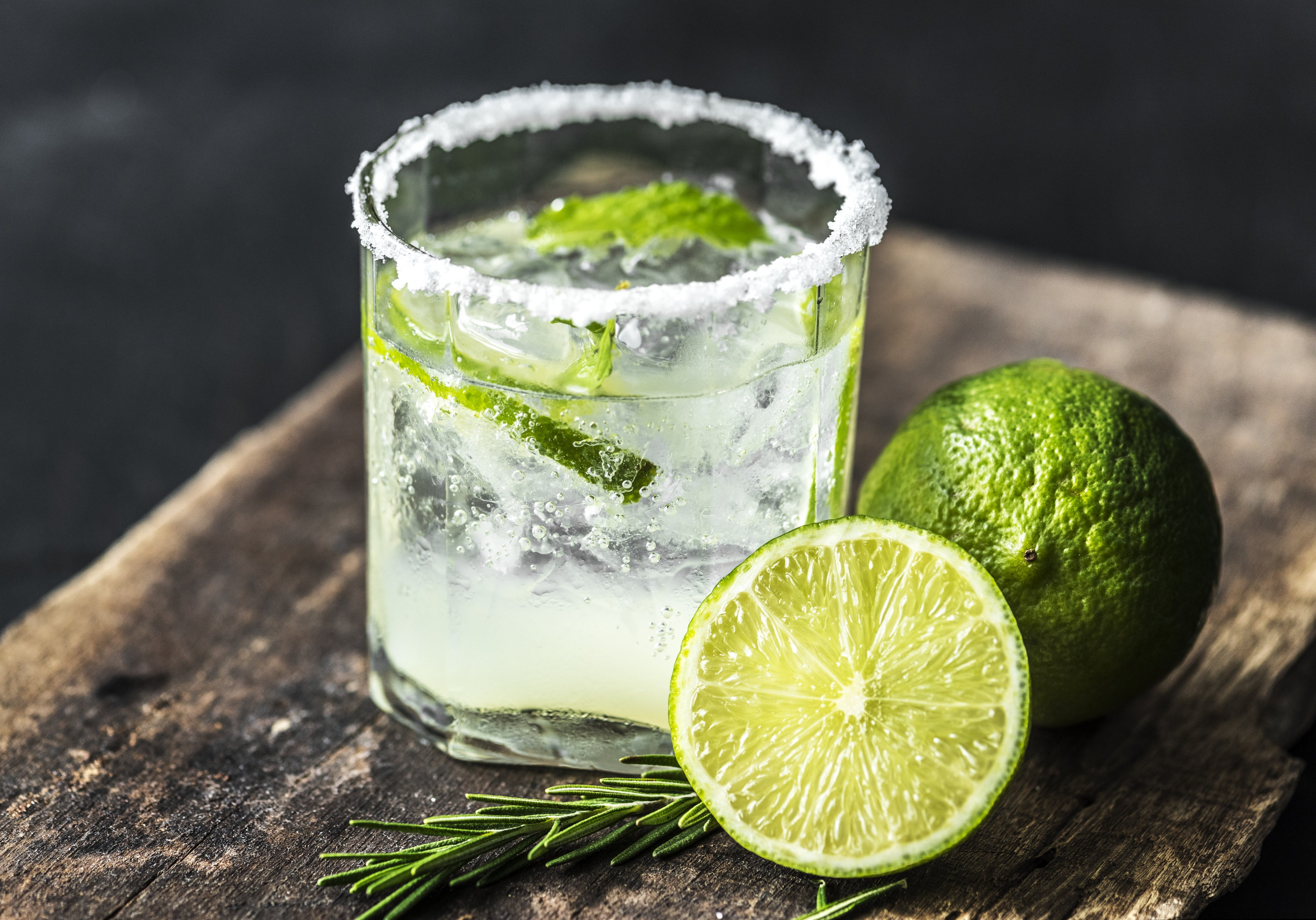 clear glass cup filled with clear liquid beside green lemons