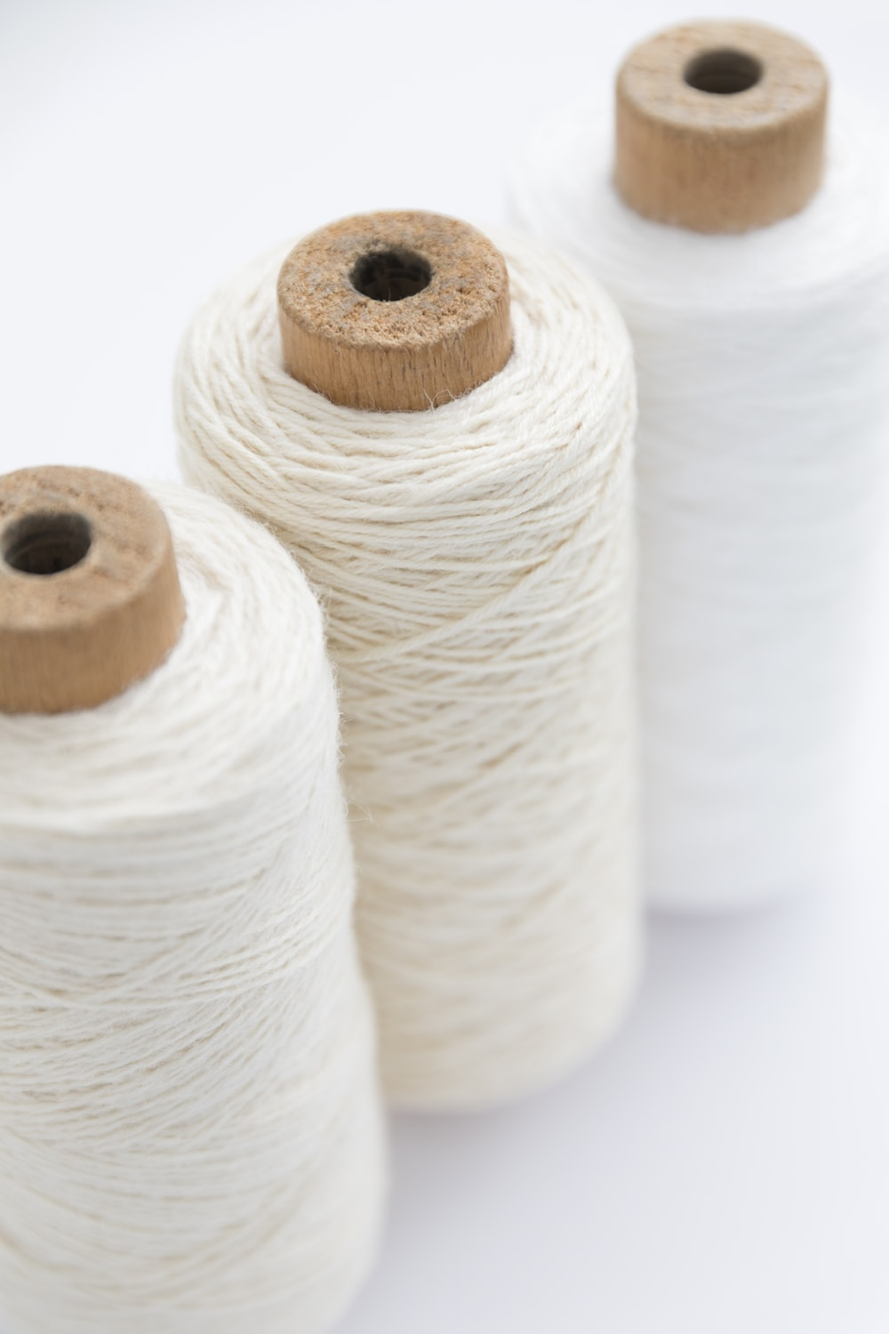 three spools of white threads