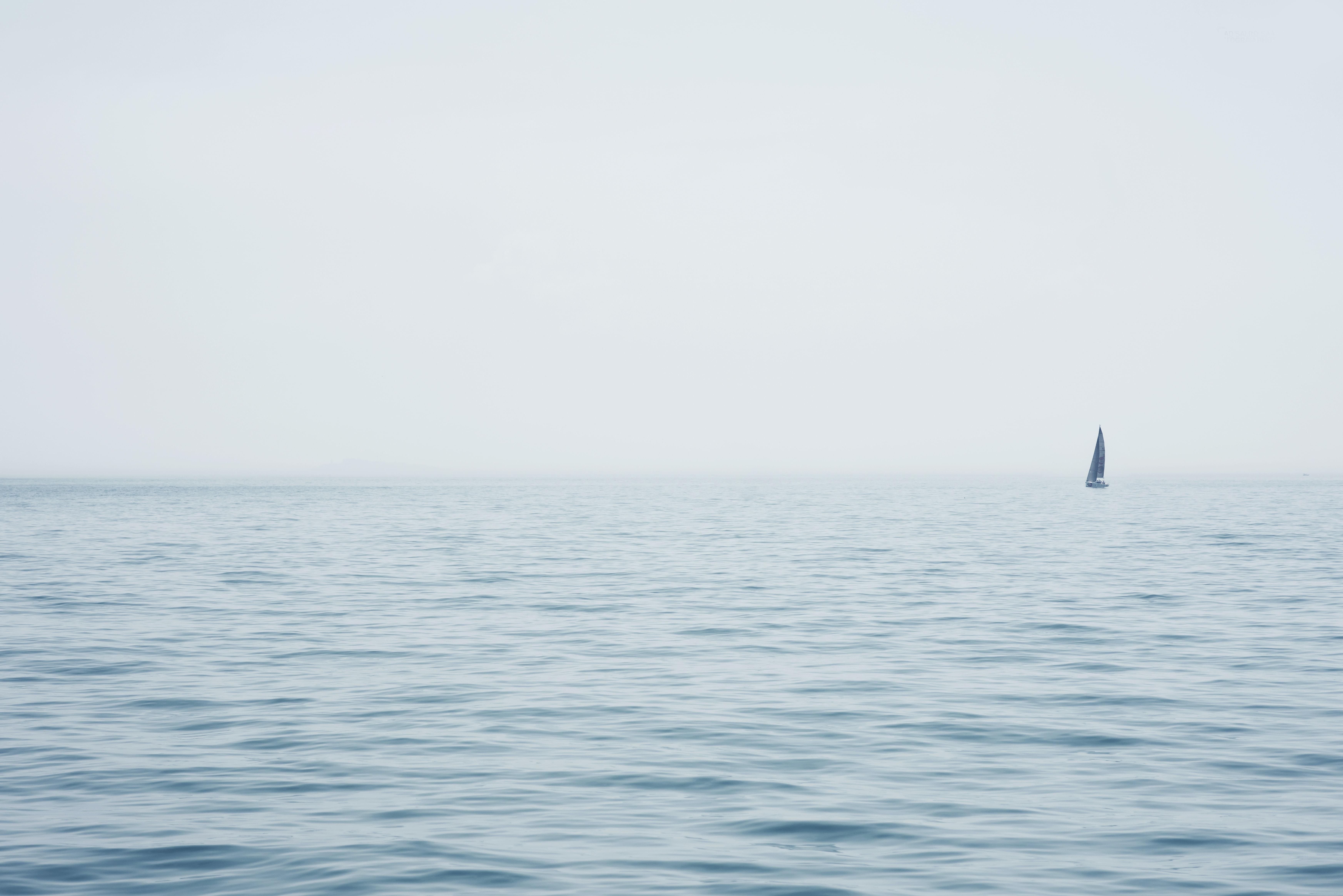 blue sailboat sailing on open sea