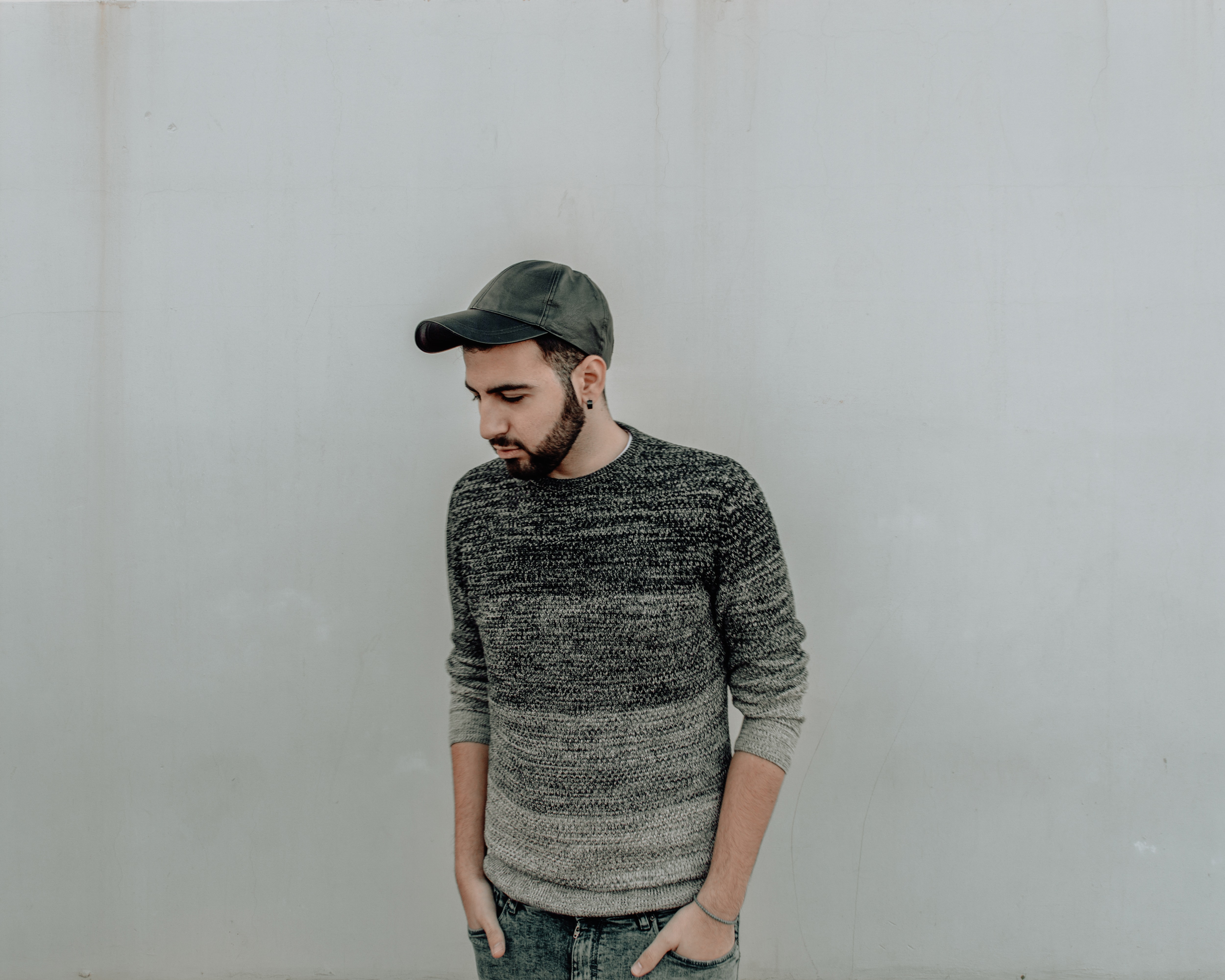 man standing on front of white wall