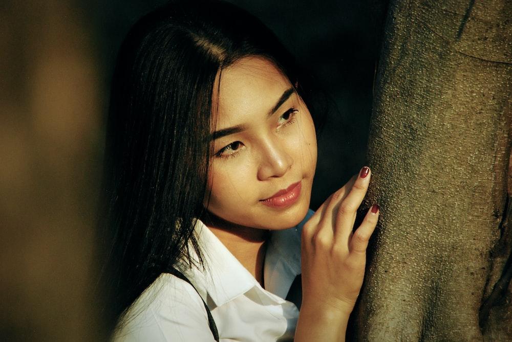 woman in white shirt near tree trunk