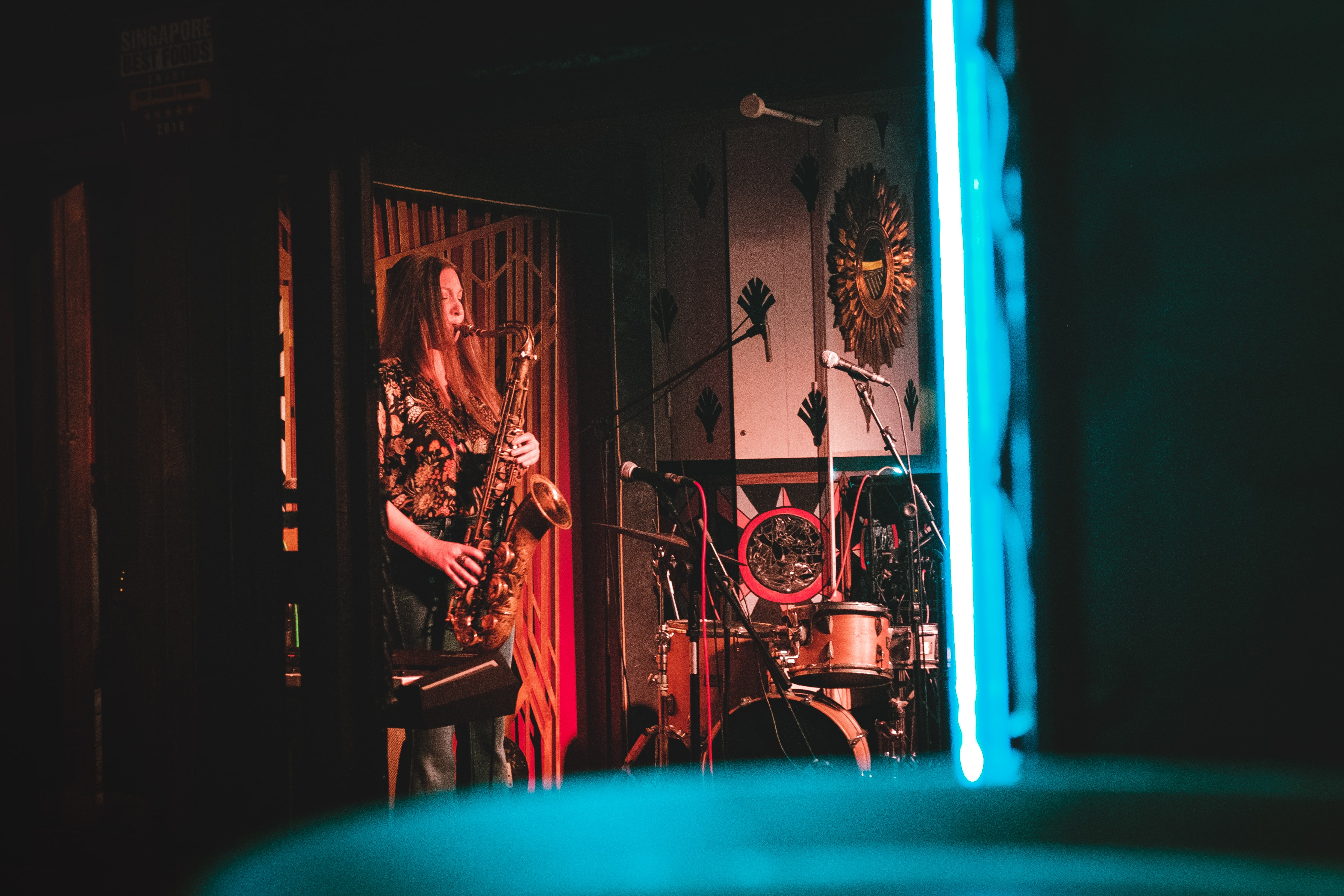 woman playing saxophone on stage near wall clock