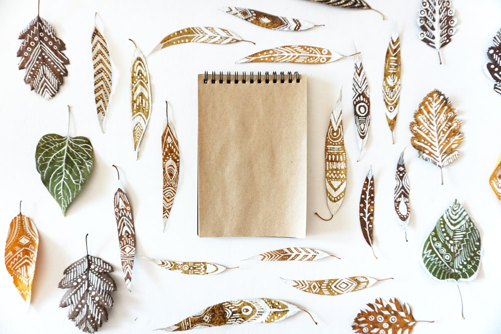 flat lay photography of tribal leaves and steno notebook