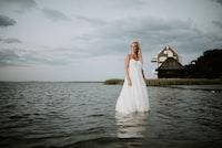 woman wearing white spaghetti strap dress above of body of water