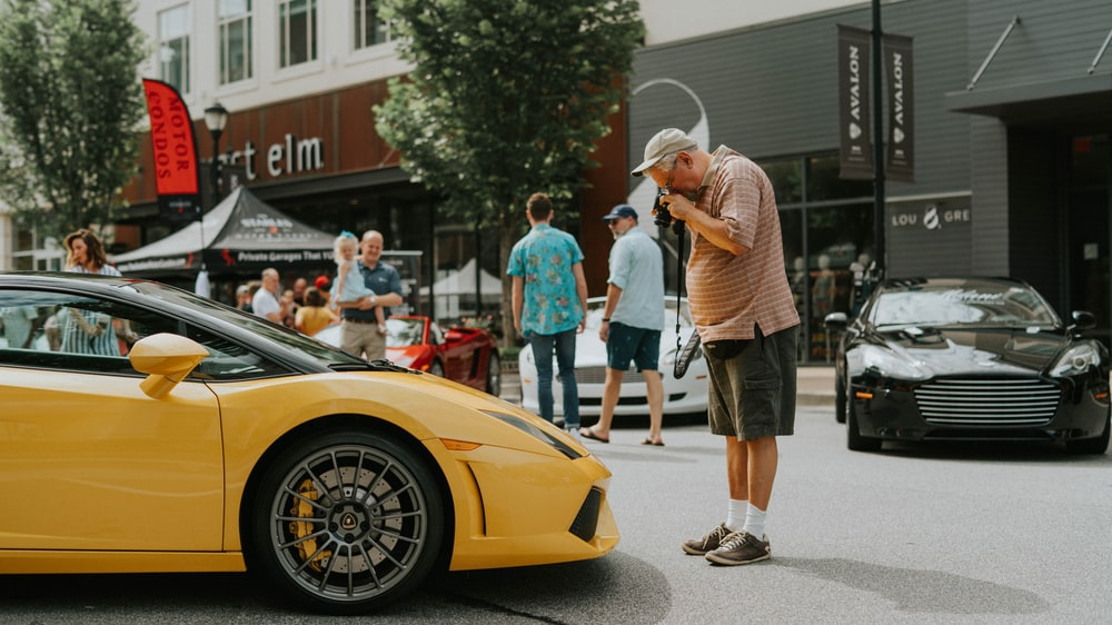 man standing in front of yellow sport car