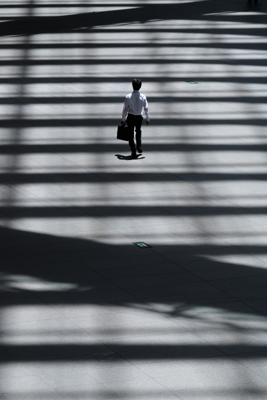 man holding laptop bag walking on street