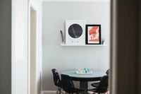 table with four chairs under two posters on wall