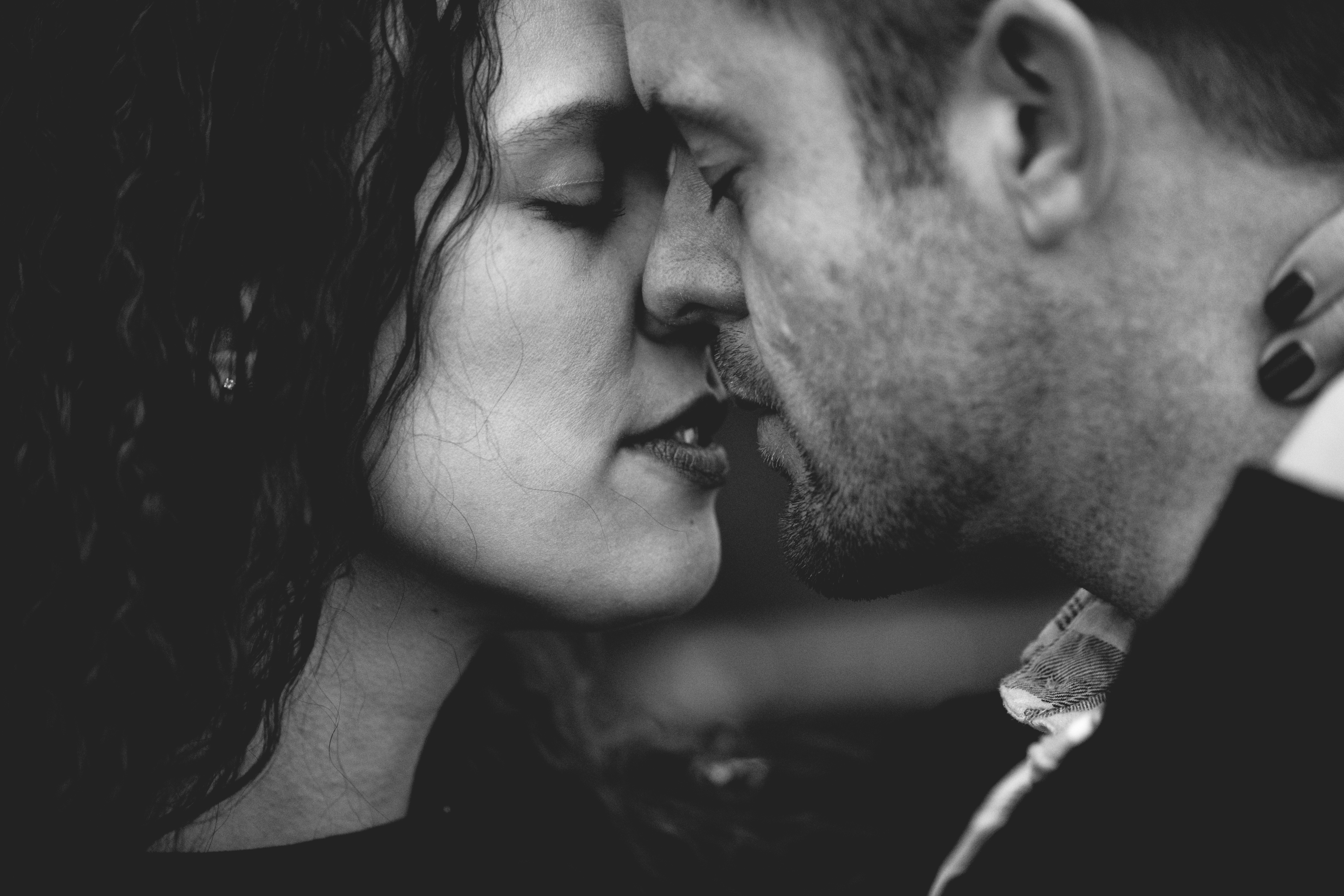 grayscale photo of man and woman kissing each other