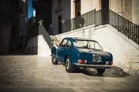 blue coupe parked beside building