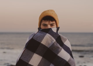 man covering his half-face with brown knit cap beside body of water at daytime