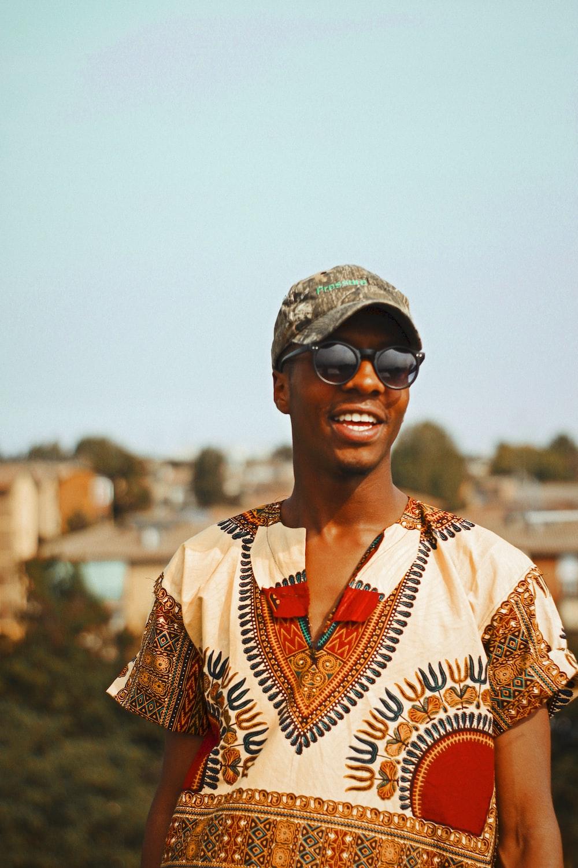 smiling man wearing brown baseball cap under clear sky