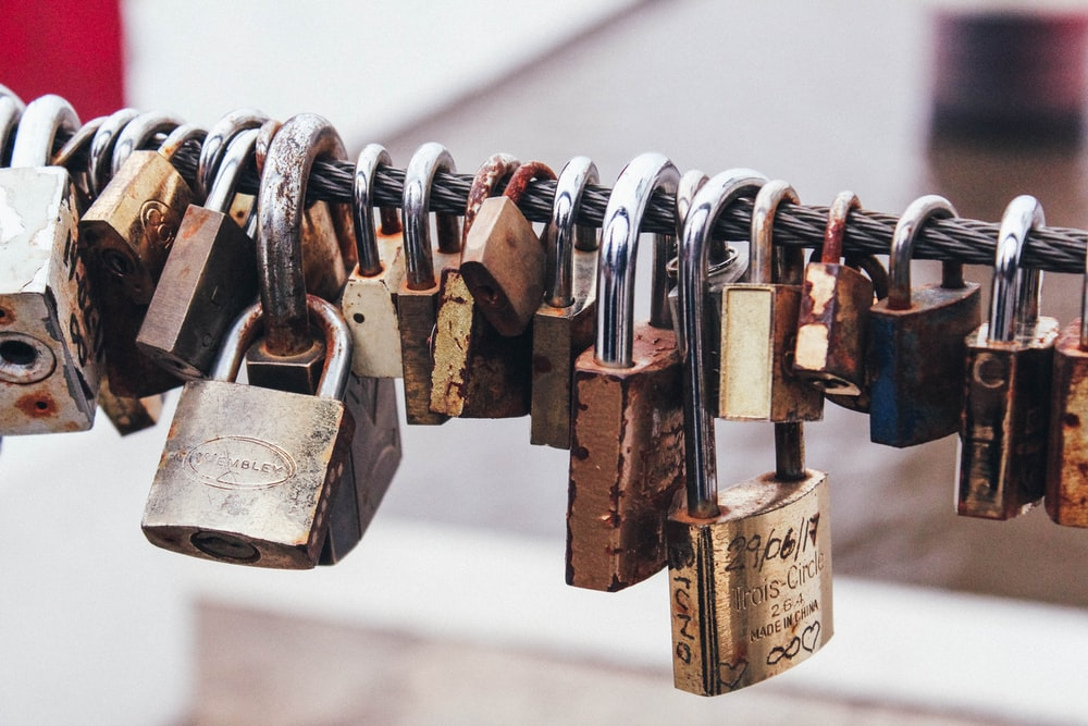 shallow focus photography of padlocks in steel cable