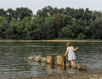 girl standing on gray stone surrounded with body of water