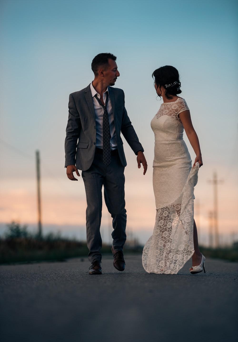 woman in wedding dress beside man in gray suit jacket