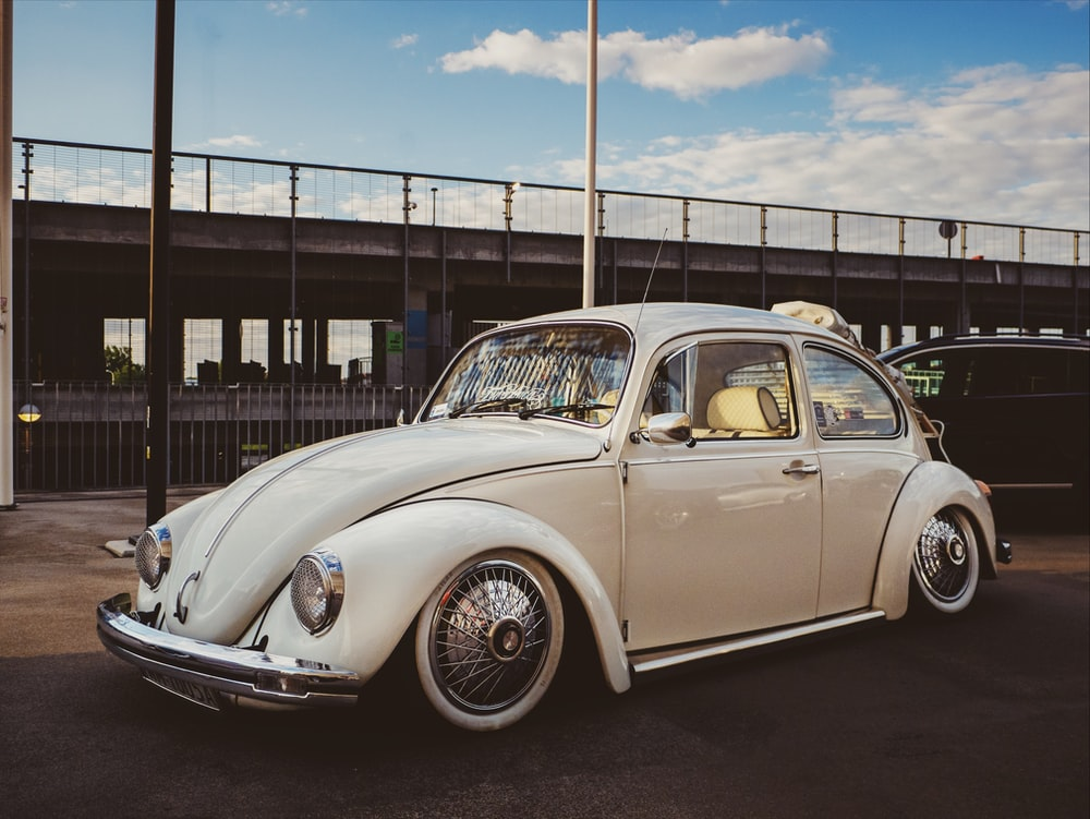 white Volkswagen Beetle hatchback parked near post