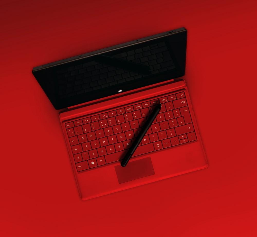 black pen on red laptop computer