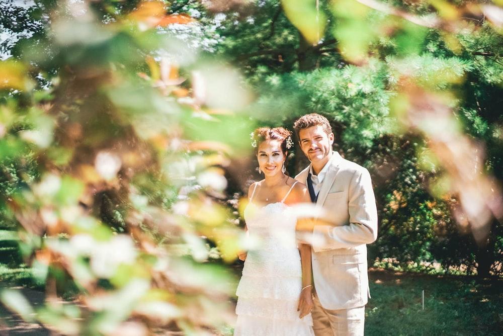 groom and bride near trees