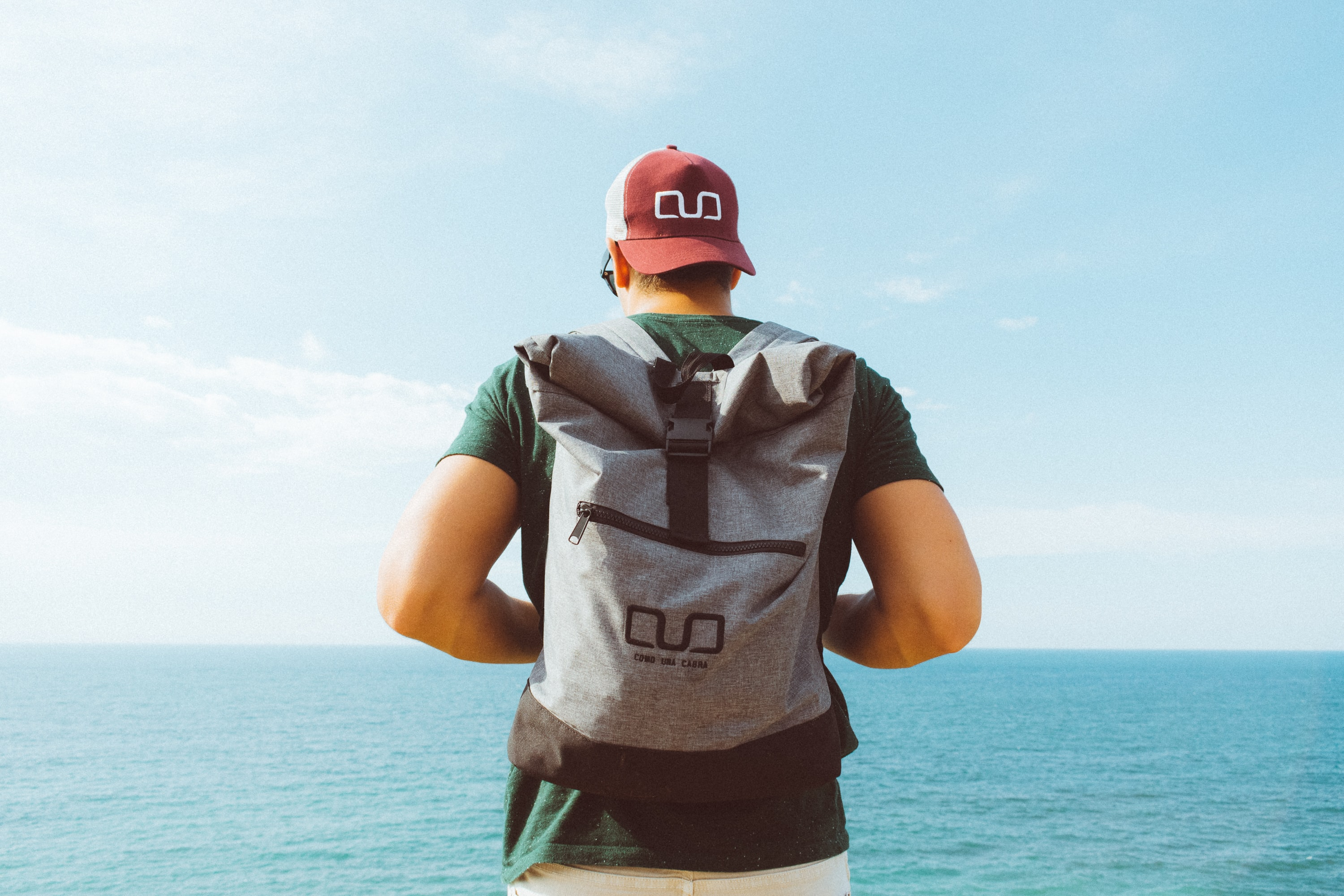 man carrying backpack standing in front of sea