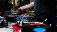 man in black shirt using DJ controller