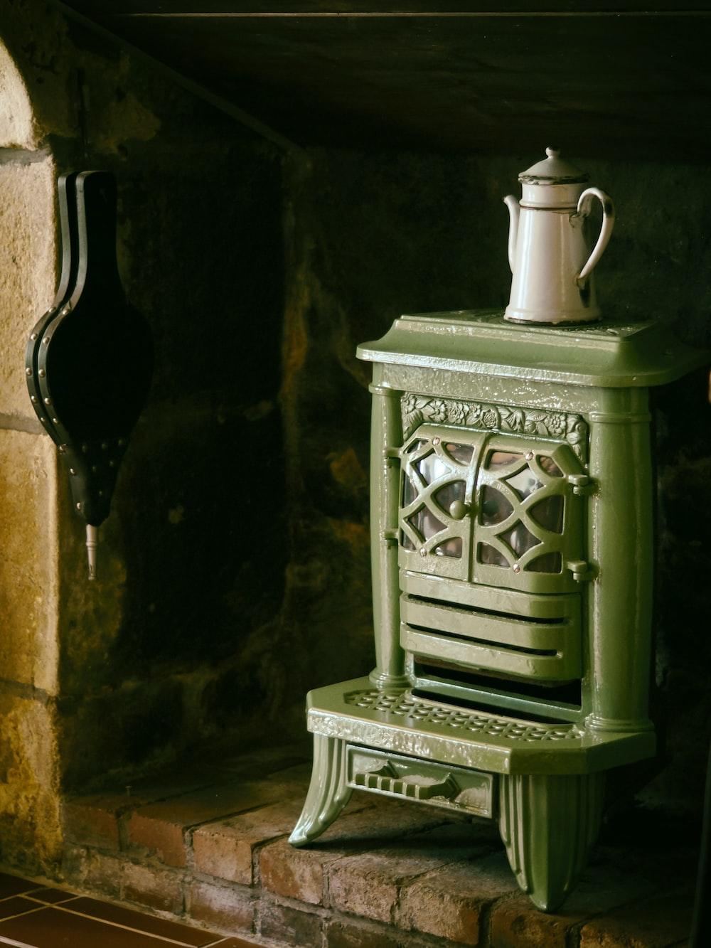 white metal teapot on green metal wood burner fireplace