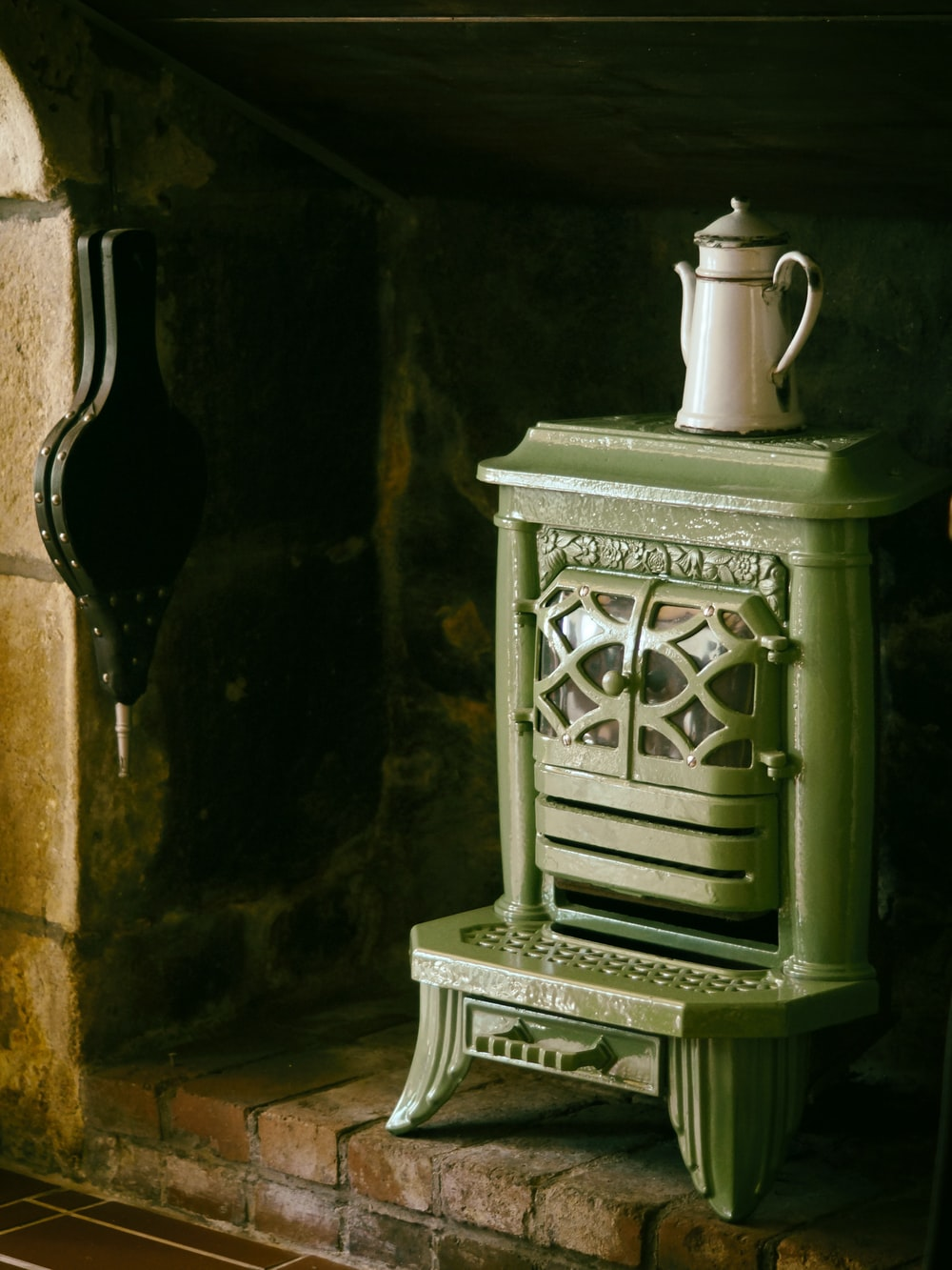 white metal teapot on green metal wood burner fireplace