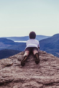 man lying on the edge of a cliff