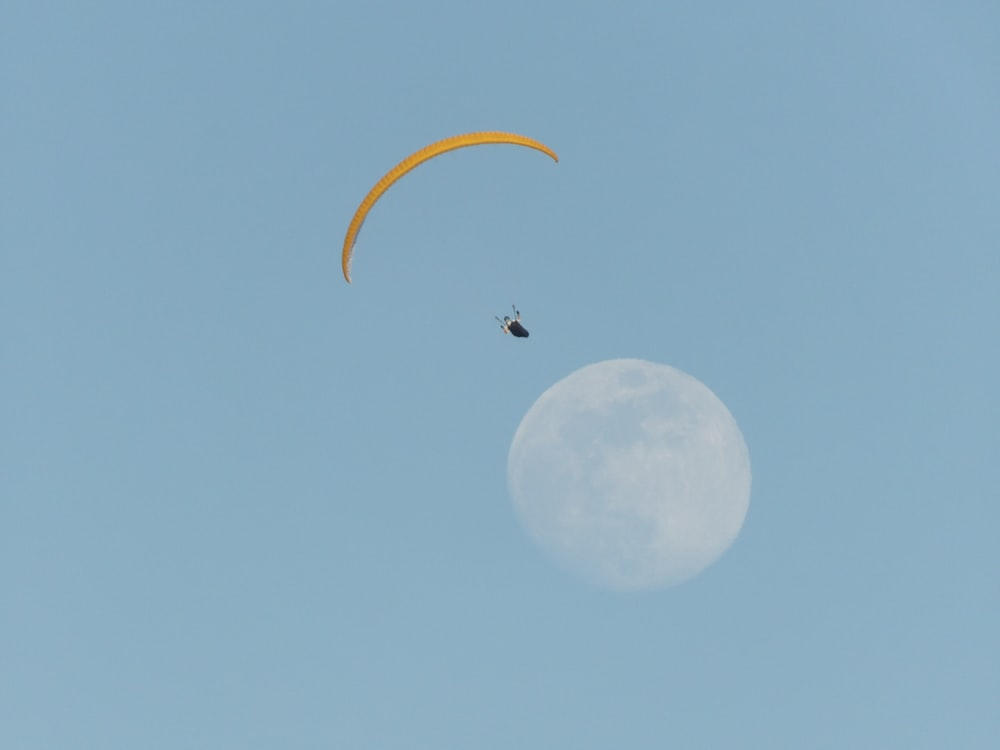 person on parachute with moon background