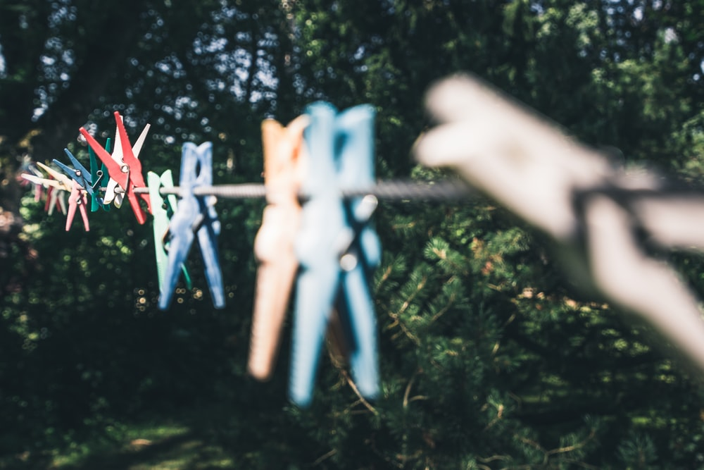 assorted-color clothes pegs on brown string selective-focus photography
