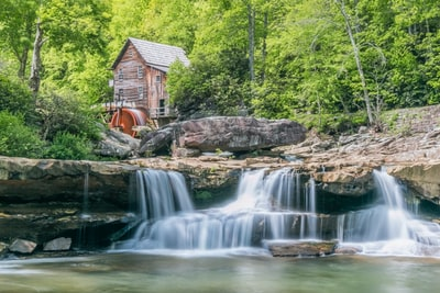brown waterfalls near house and forest trees during daytime west virginia teams background