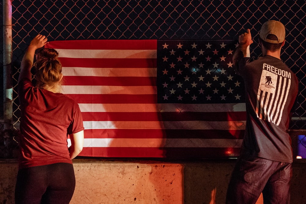 woman and man holding U.S.A. flag near gray wire fence