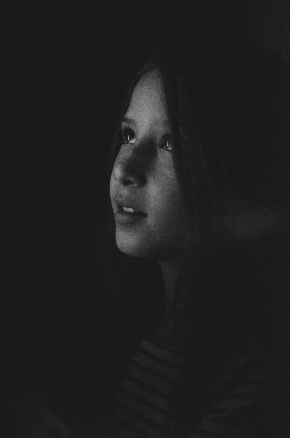 grayscale photography of a girl looking up