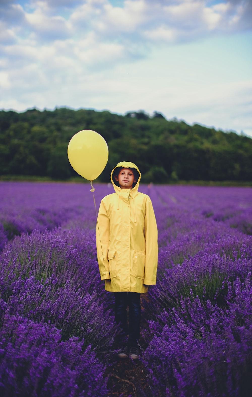 woman in yellow dress shirt near purple flower field