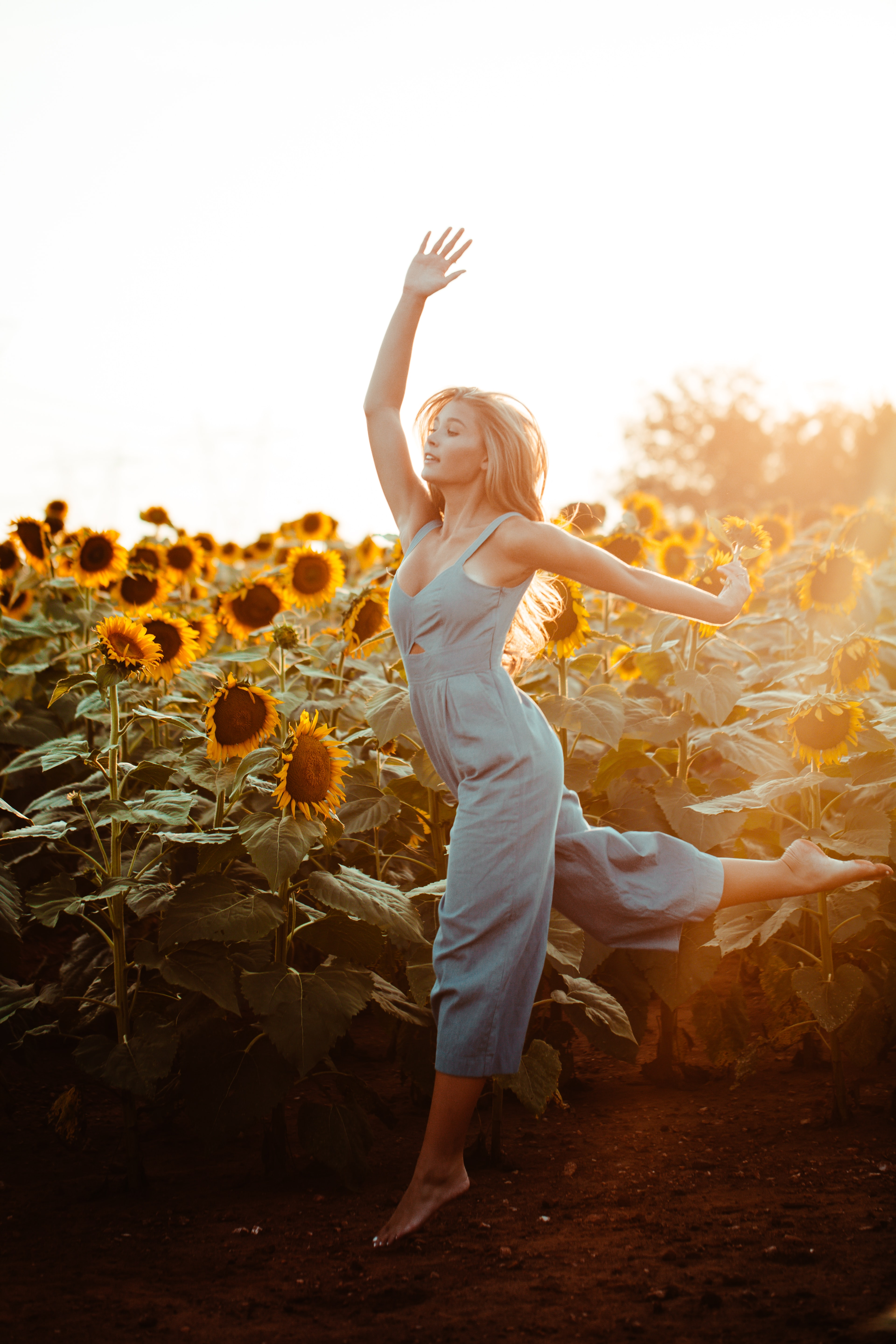 close up photography of woman dancing beside sunflower field during golden hour