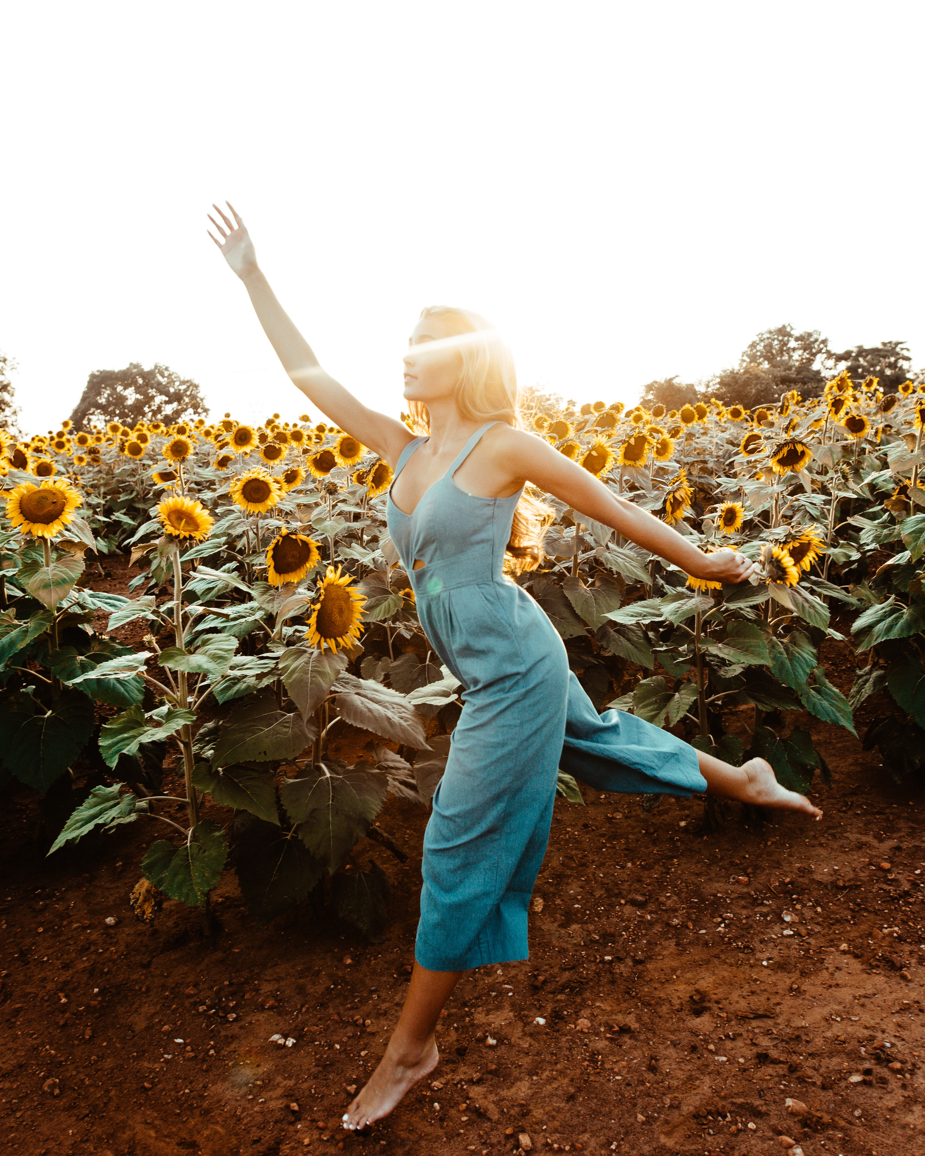 woman wearing green sleeveless rompers standing and waving hands near garden of sunflower at daytime