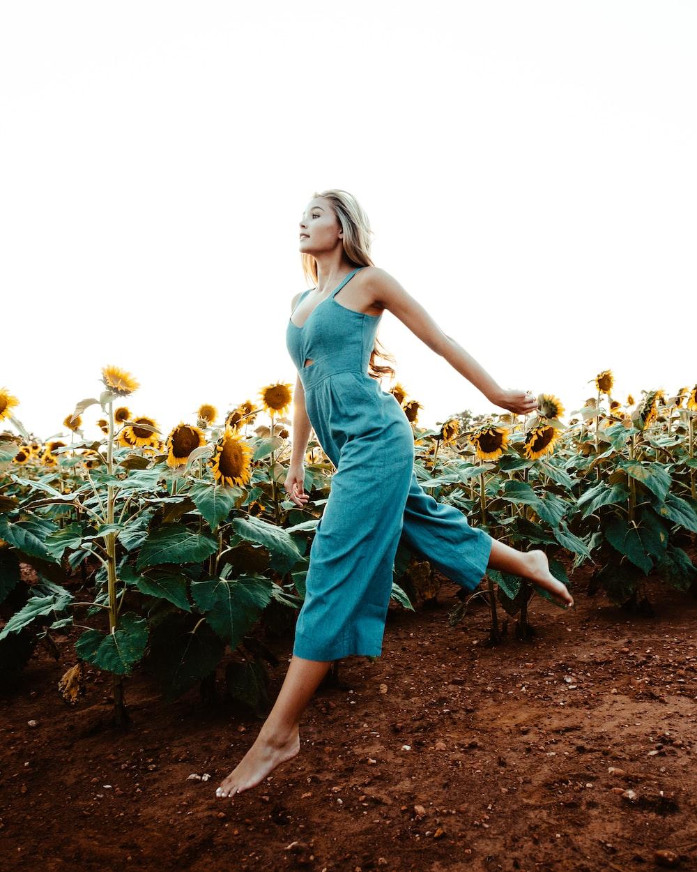 woman walking near the sunflower field at daytime