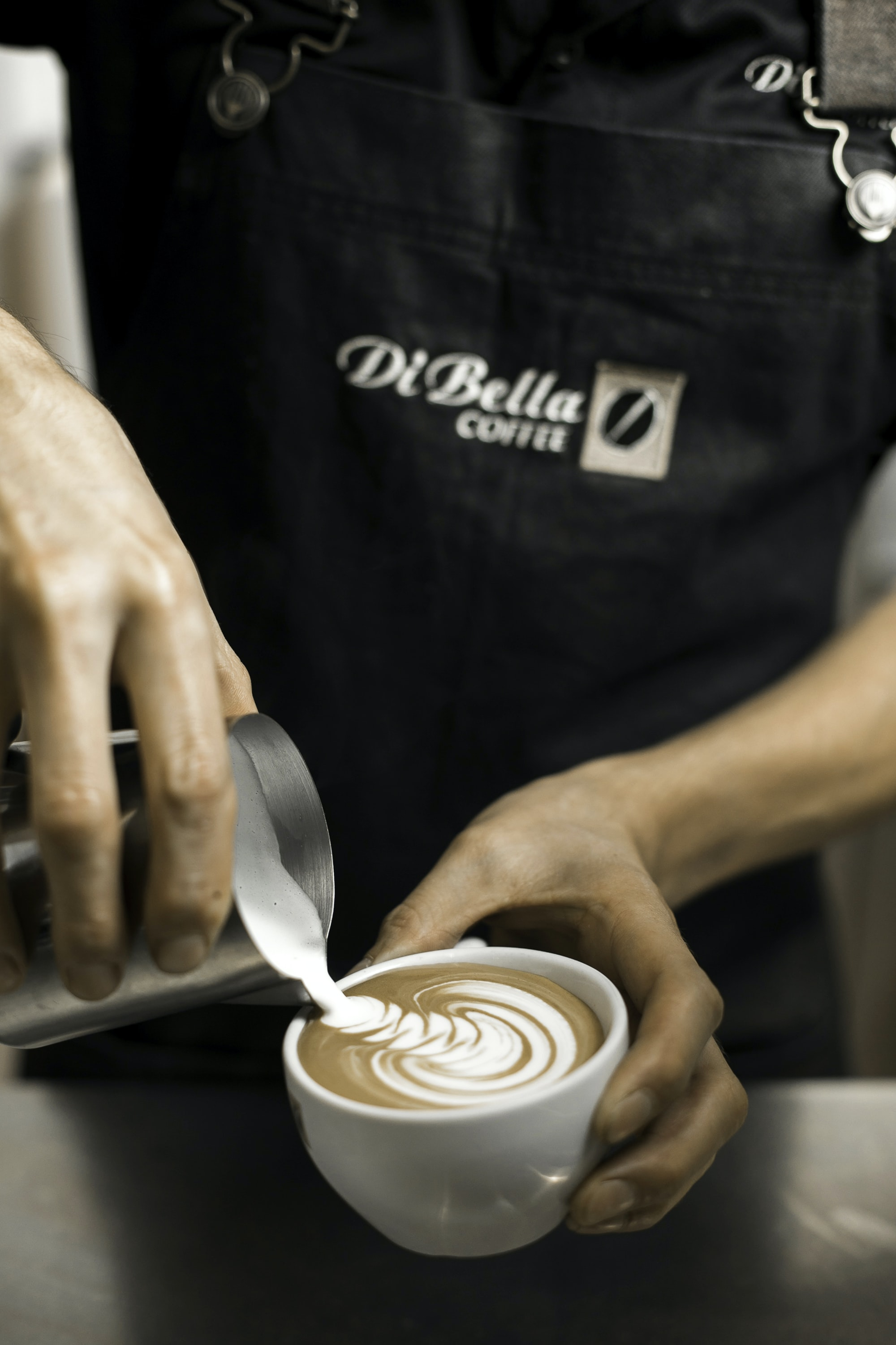 person holding cup making latte art