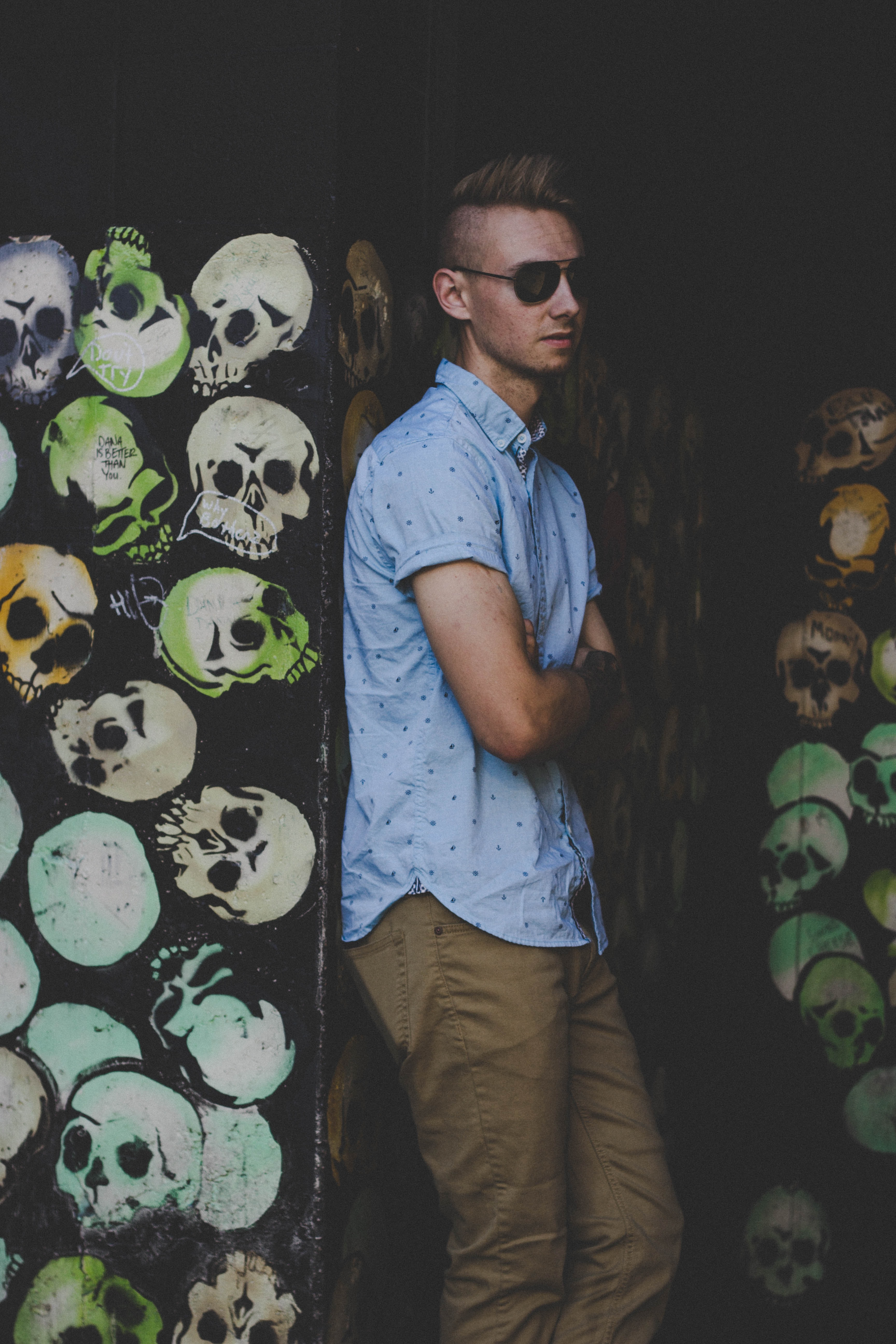 men wearing blue button-up shirt leaning on black graffitied wall