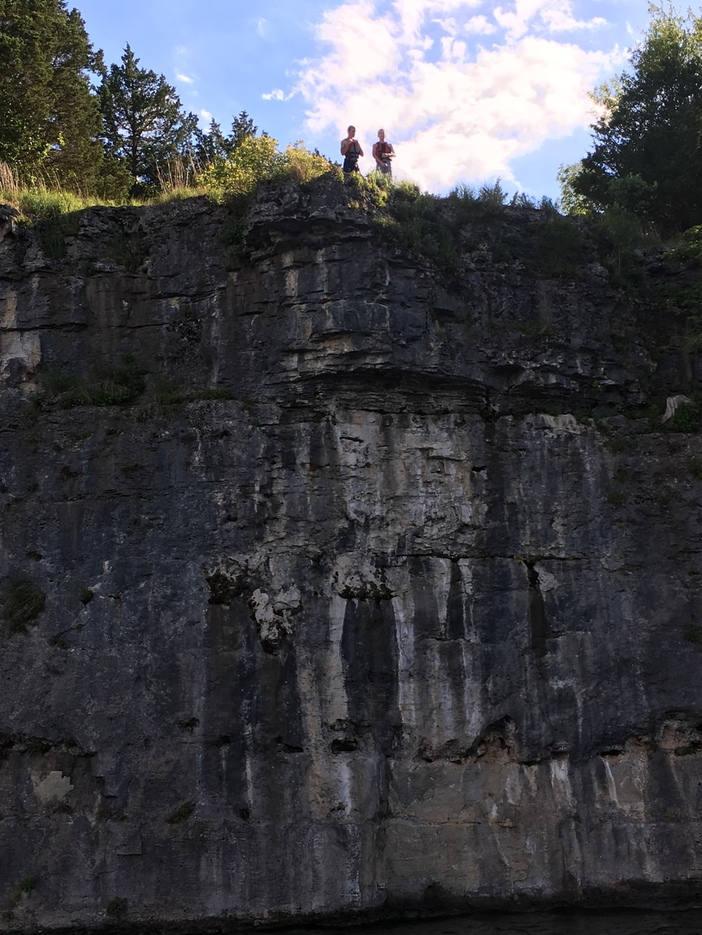 two men's standing near cliff over sky at daytime