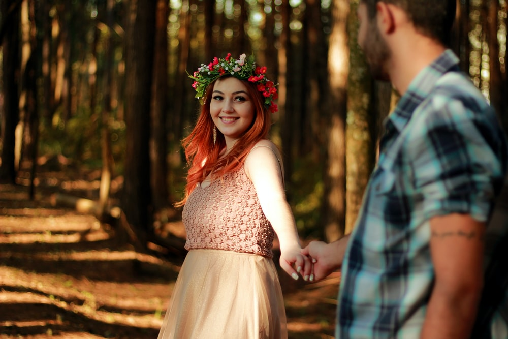 couple holding hands while standing near tree barks