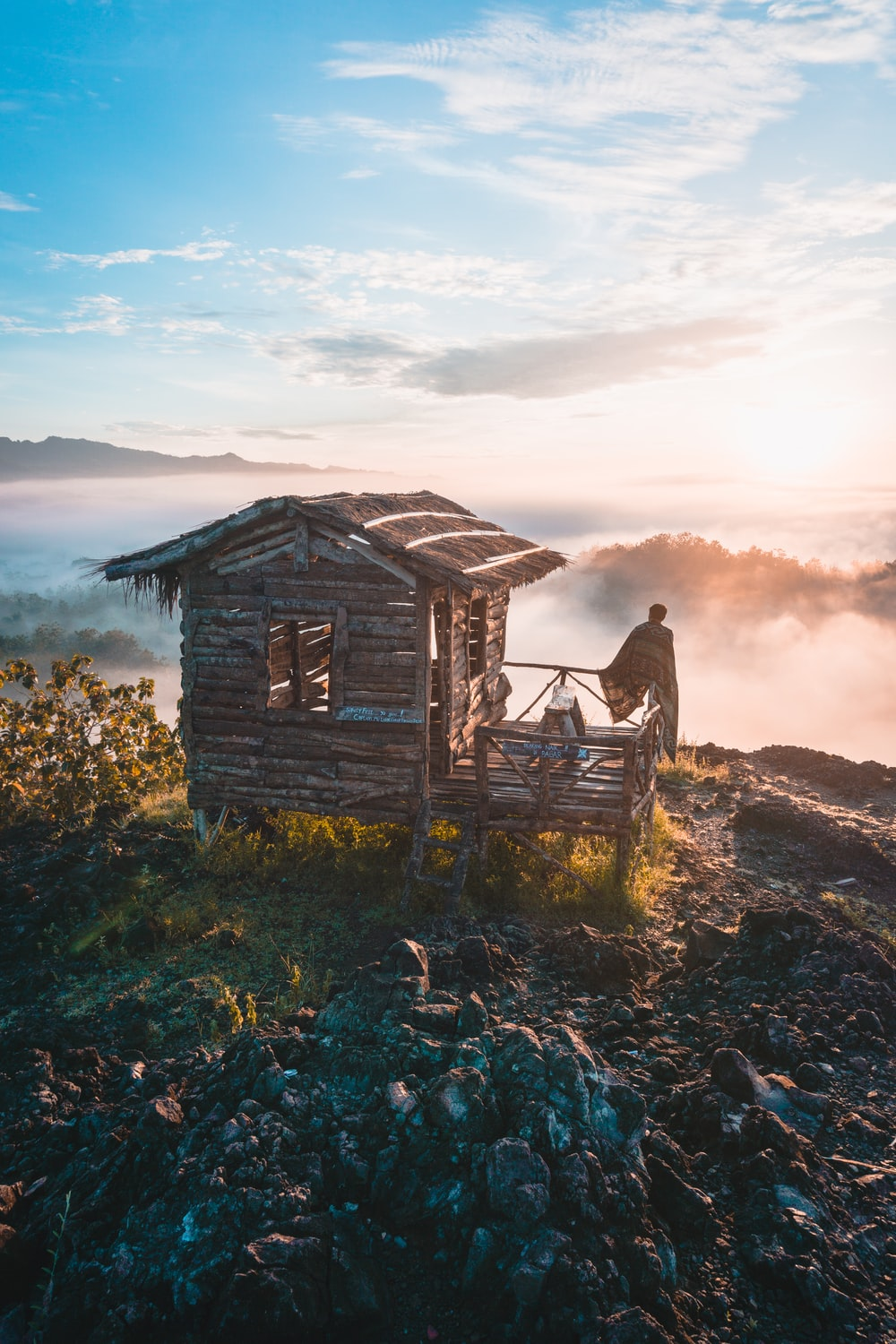 person in wooden cabin on hill