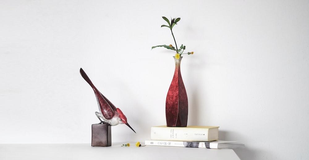 white and maroon bird figurine near red vase