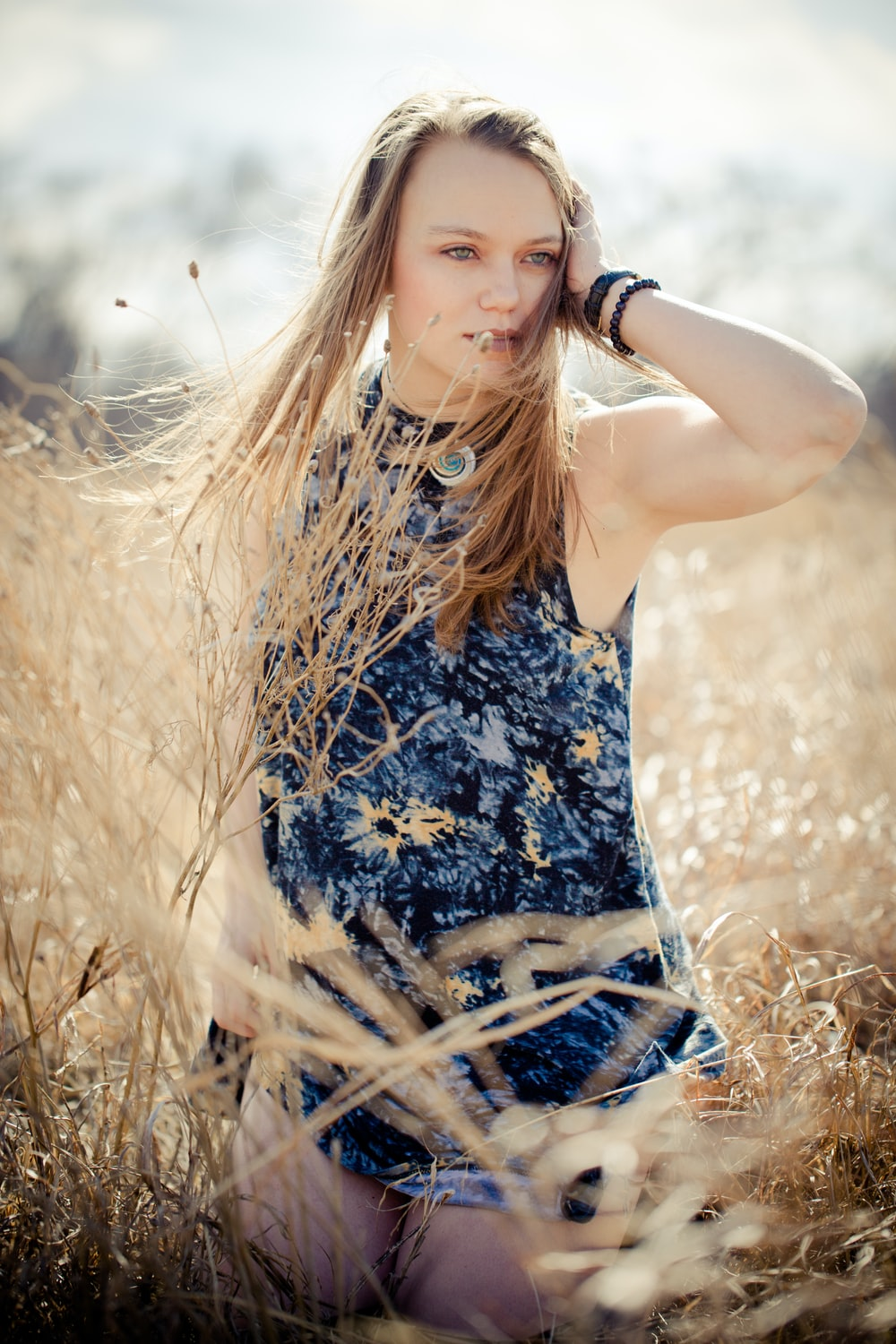 close up photography of woman standing between brown grasses during daytime