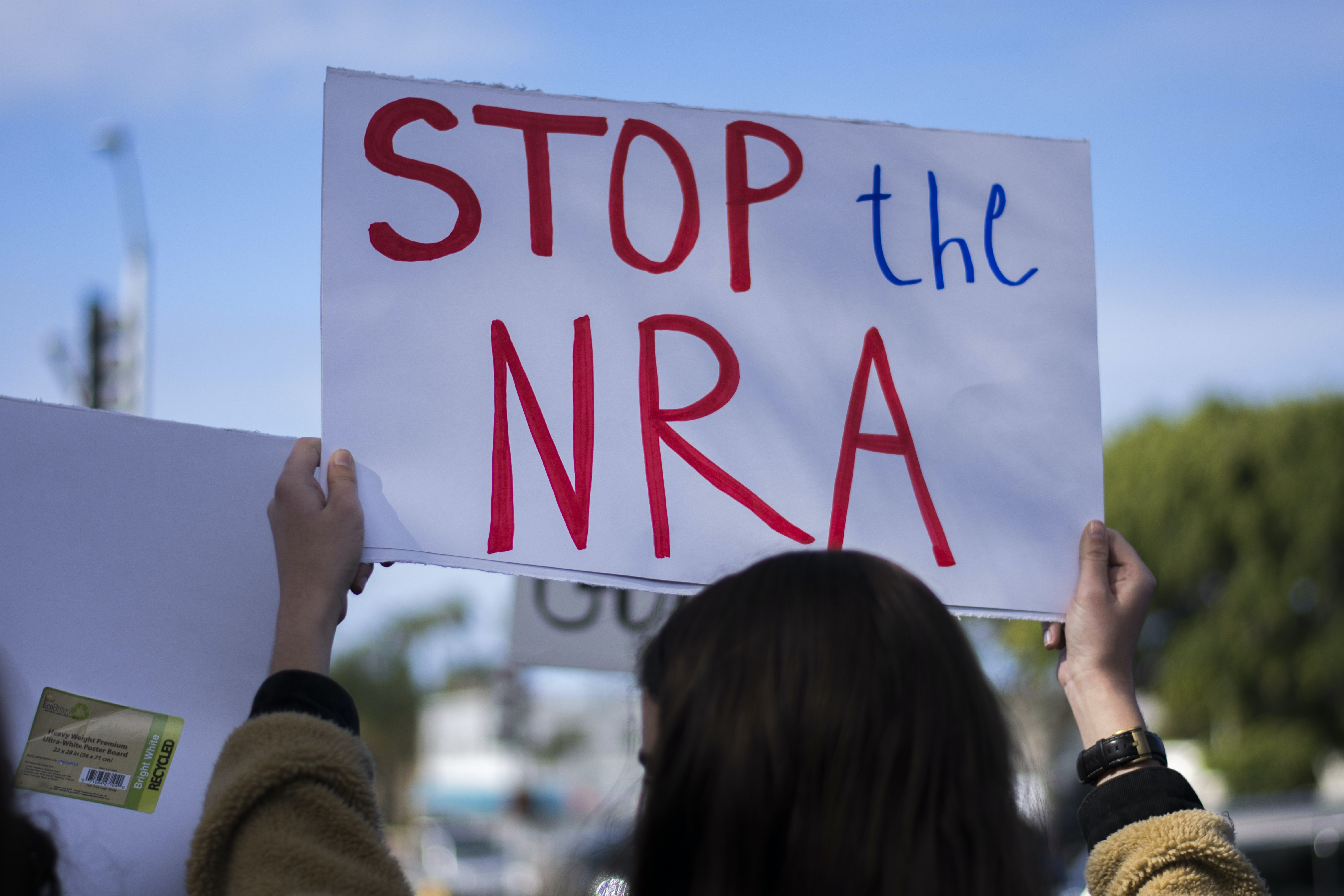 woman holding Stop the NRA banner