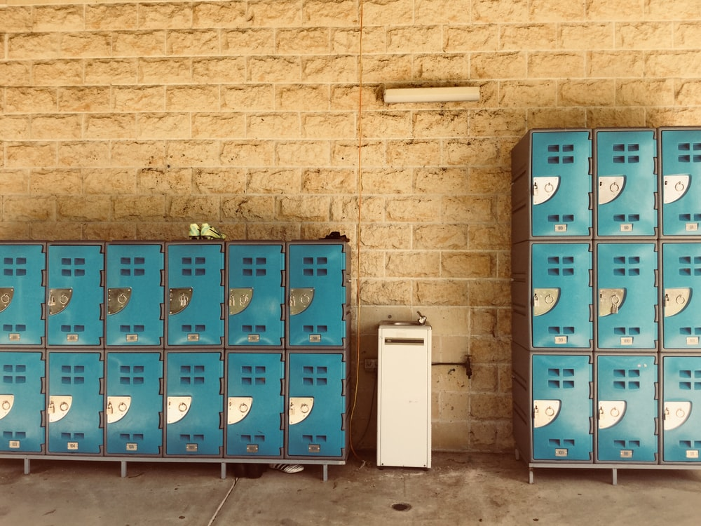 closed teal lockers with beside wall