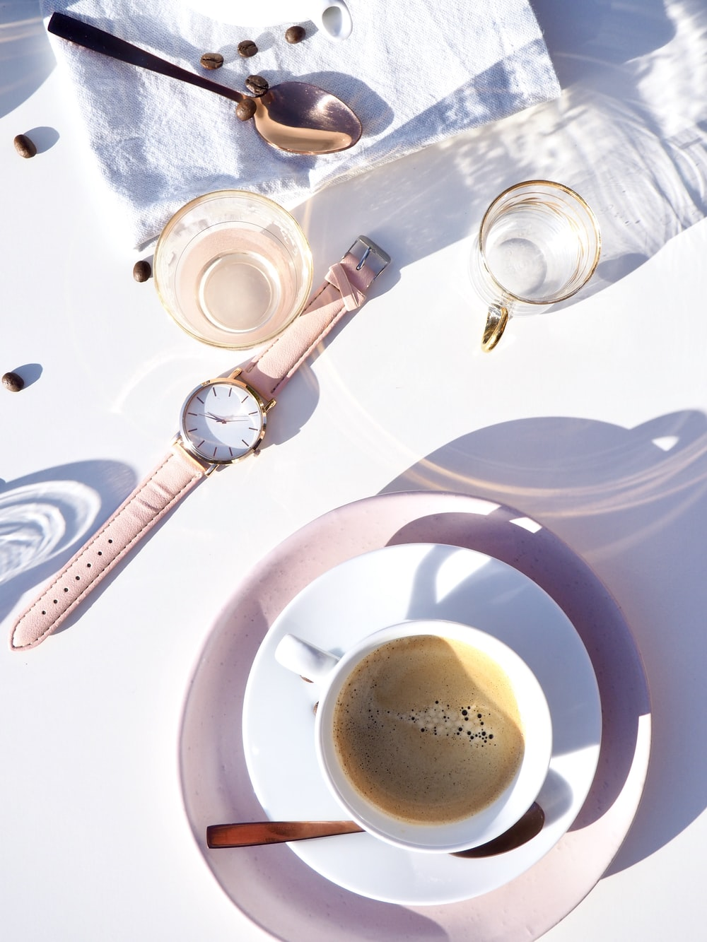 round gold-colored analog watch displaying 12:41 near cup of coffee