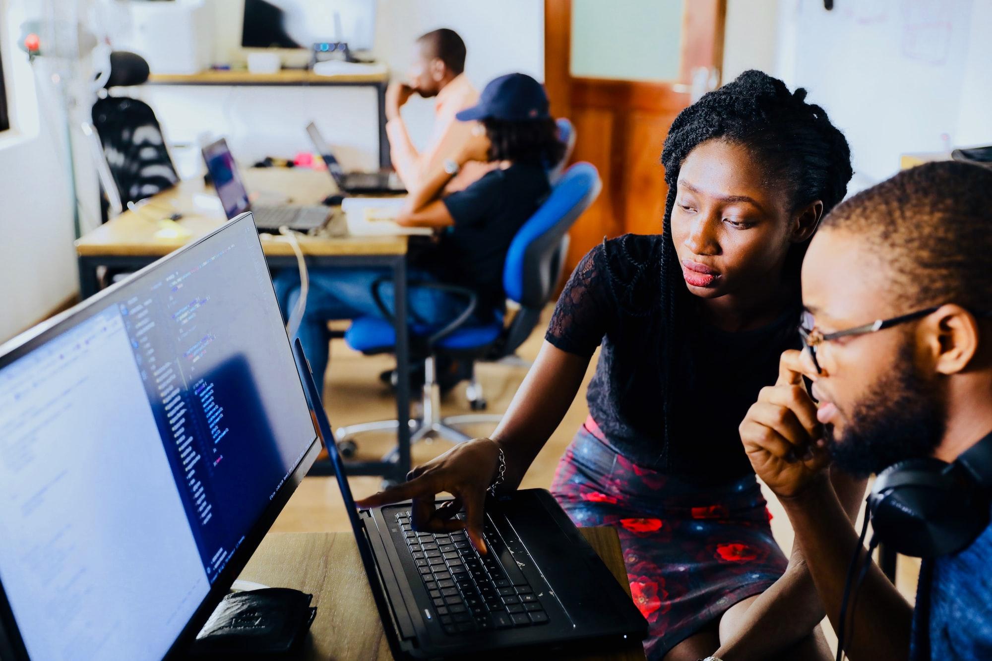 Um time de analytics formado por uma mulher e um homem, que estão sentados em frente a duas telas de computador, analisando dados. Os dois são negros, a mulher está de saia até os joelhos e uma blusa preta, apontando para algo no computador. O homem está de óculos, com um headphone no pescoço, olhando para onde a mulher está apontando.