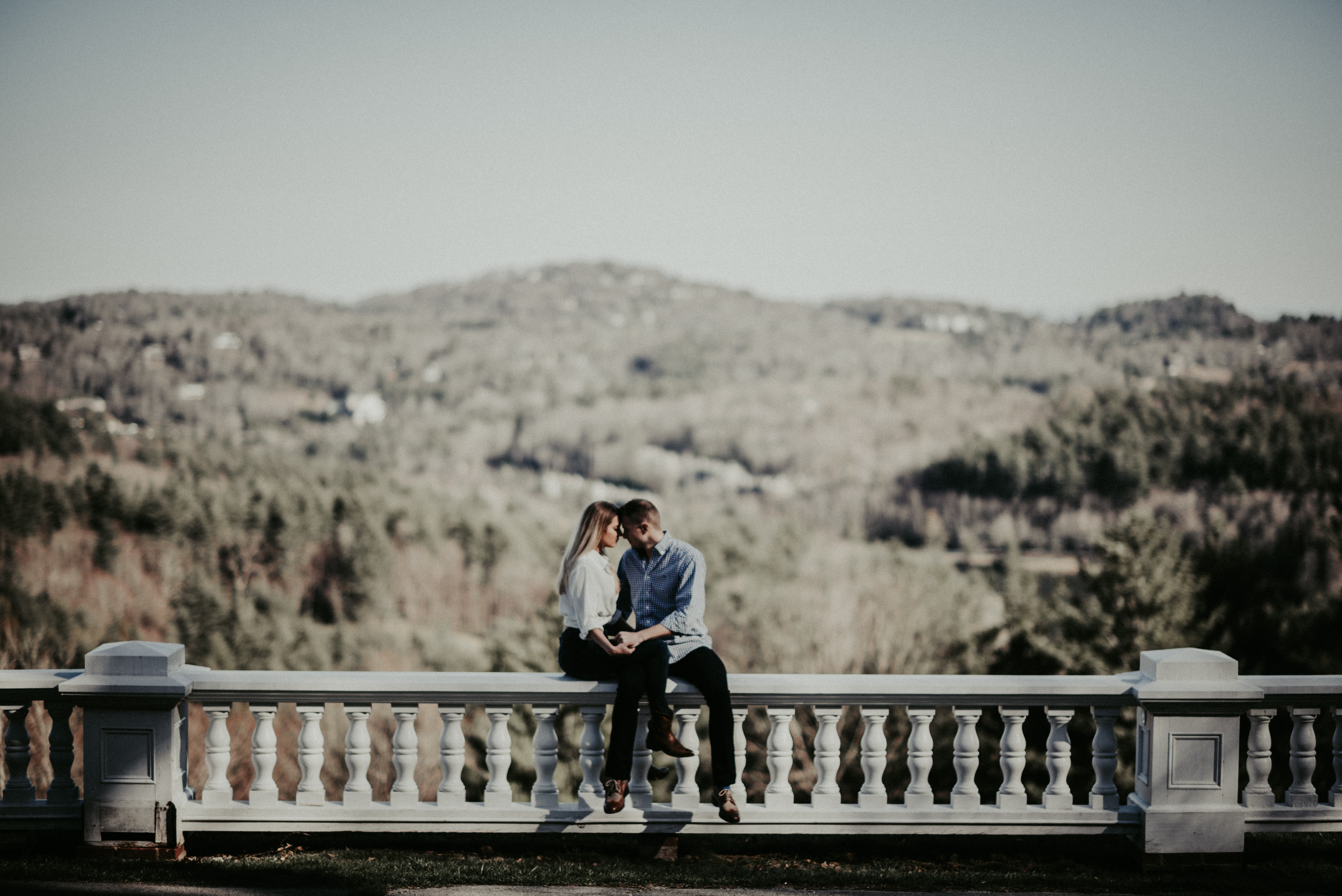 couple sitting on ledge in distant of mountain