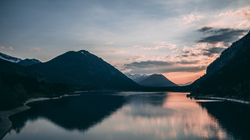 silhouette of mountain beside body of water