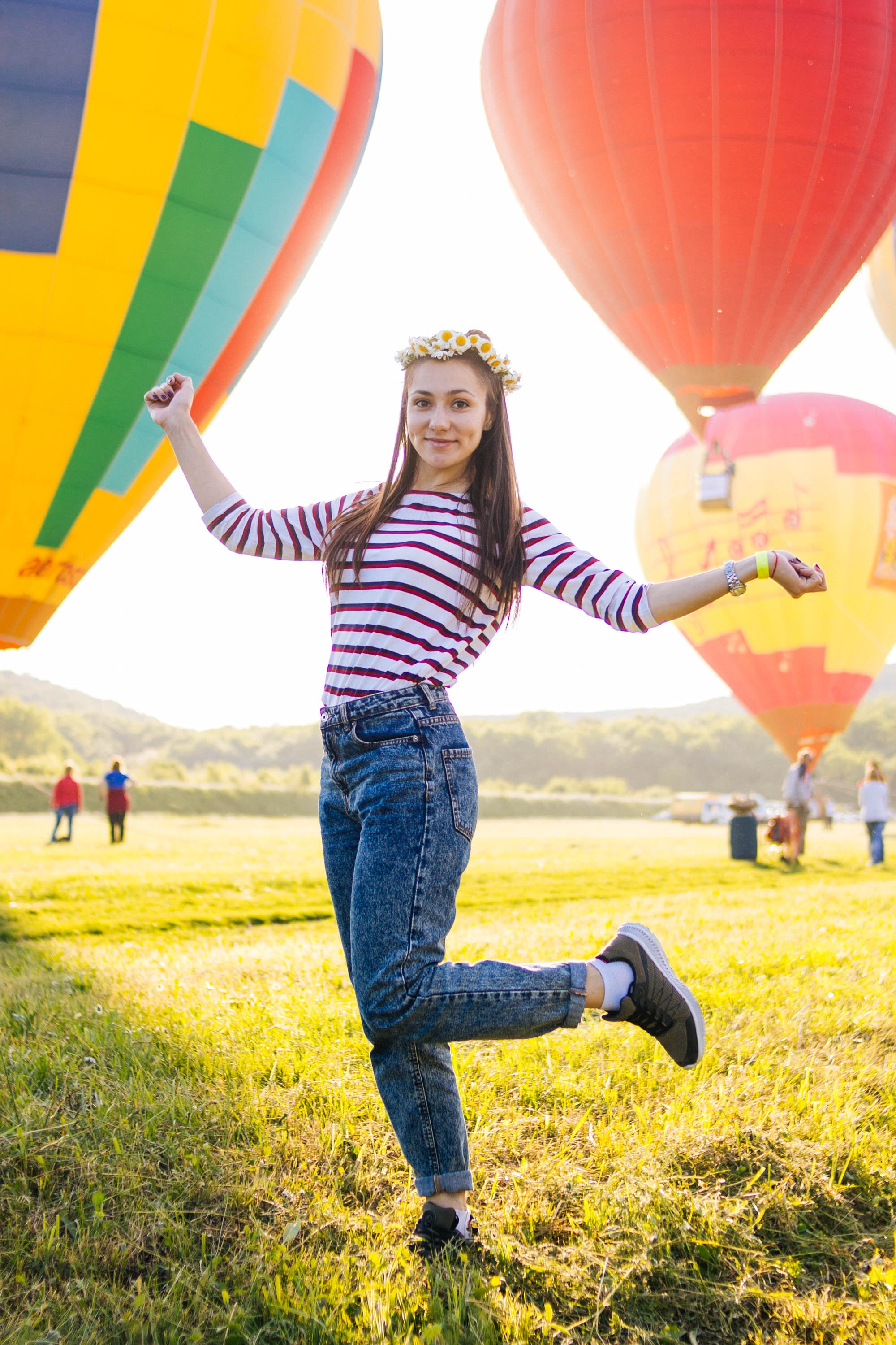 woman posing on grass field surrounded with hot air balloons