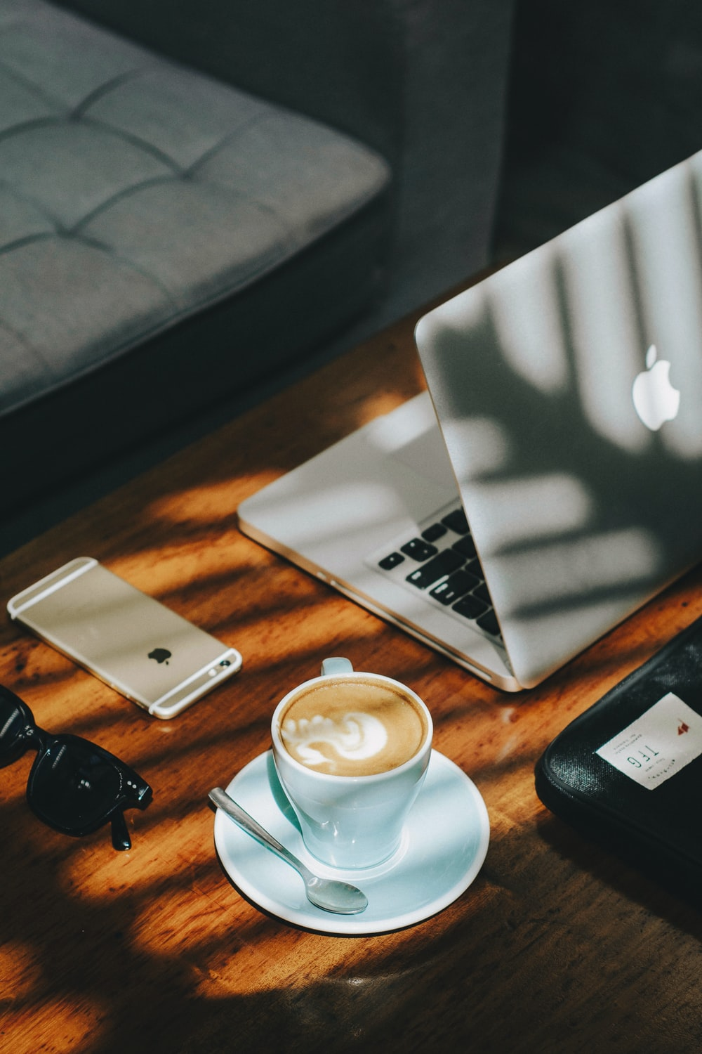 cappuccino in white ceramic cup with saucer beside gold iPhone 6s and laptop